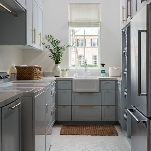 Inspiration for a huge transitional u-shaped brick floor and white floor dedicated laundry room remodel in Houston with a farmhouse sink, recessed-panel cabinets, blue cabinets, white walls, a side-by-side washer/dryer and white countertops