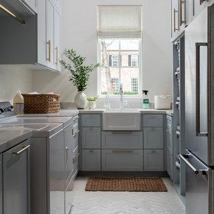 Esempio di un'ampia sala lavanderia classica con lavello stile country, ante con riquadro incassato, ante blu, pareti bianche, pavimento in mattoni, lavatrice e asciugatrice affiancate, pavimento bianco e top bianco