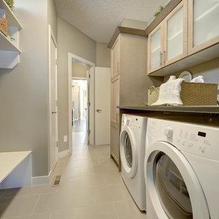 Inspiration för mellanstora moderna linjära tvättstugor enbart för tvätt, med luckor med glaspanel, skåp i ljust trä, grå väggar och en tvättmaskin och torktumlare bredvid varandra
