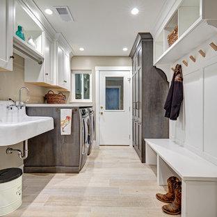 Diseño de lavadero multiusos y de galera, ecléctico, de tamaño medio, con pila para lavar, armarios con paneles empotrados, puertas de armario grises, encimera de cuarzo compacto, paredes beige, suelo de baldosas de porcelana y lavadora y secadora juntas