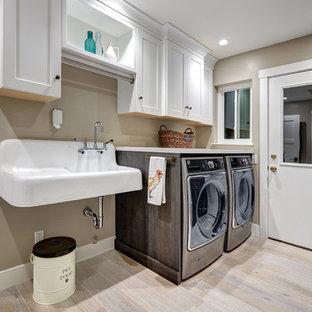 Inspiration för en mellanstor lantlig tvättstuga, med en allbänk, luckor med infälld panel, vita skåp, bänkskiva i kvarts, beige väggar, klinkergolv i porslin, en tvättmaskin och torktumlare bredvid varandra och beiget golv