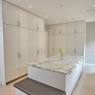 Immagine di un'ampia lavanderia multiuso moderna con lavello sottopiano, ante lisce, ante bianche, top in quarzite, pareti grigie, lavatrice e asciugatrice affiancate e pavimento marrone