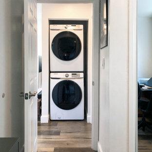Inspiration för en liten vintage vita parallell vitt liten tvättstuga, med vita väggar, mellanmörkt trägolv, en tvättpelare, brunt golv, släta luckor, vita skåp och bänkskiva i kvarts