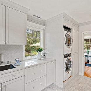 Идея дизайна: прямая универсальная комната среднего размера в классическом стиле с врезной раковиной, фасадами в стиле шейкер, белыми фасадами, столешницей из кварцевого агломерата, серым фартуком, фартуком из керамической плитки, белыми стенами, полом из керамической плитки, с сушильной машиной на стиральной машине, серым полом и белой столешницей