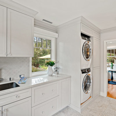 Mid-sized elegant single-wall ceramic tile and gray floor utility room photo in San Francisco with an undermount sink, shaker cabinets, white cabinets, quartz countertops, gray backsplash, ceramic backsplash, white walls, a stacked washer/dryer and white countertops