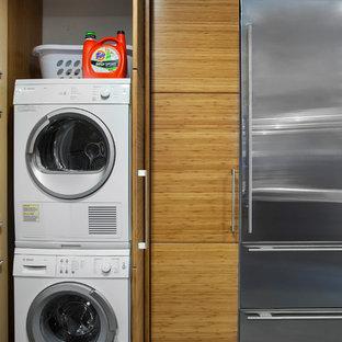 Esempio di un ripostiglio-lavanderia minimalista con lavatrice e asciugatrice nascoste