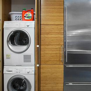 Example of a minimalist laundry closet design in Austin with a concealed washer/dryer