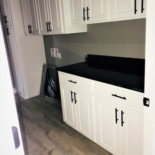 Design ideas for a large contemporary utility room in New Orleans with an utility sink, white cabinets, granite worktops, grey walls, light hardwood flooring, a side by side washer and dryer, white floors and black worktops.