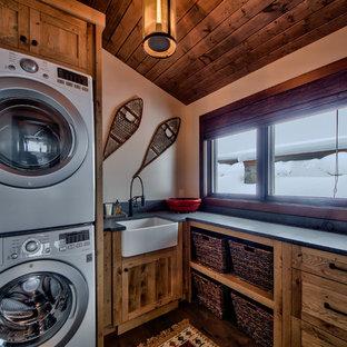 Idee per una sala lavanderia stile rurale di medie dimensioni con lavello stile country, ante lisce, top in cemento, pareti beige, pavimento in legno massello medio, lavatrice e asciugatrice a colonna e ante in legno scuro