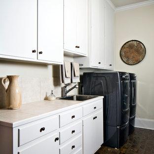 Idéer för stora vintage parallella grovkök, med en nedsänkt diskho, släta luckor, vita skåp, kaklad bänkskiva, vita väggar, tegelgolv och en tvättmaskin och torktumlare bredvid varandra