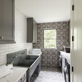 Exemple d'une buanderie parallèle nature dédiée avec un évier utilitaire, un placard à porte shaker, des portes de placard grises, des machines côte à côte, un sol multicolore, un plan de travail blanc et un mur gris.