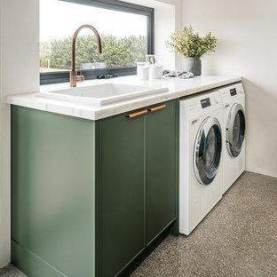 Ispirazione per una lavanderia multiuso contemporanea di medie dimensioni con lavello da incasso, ante in stile shaker, ante verdi, top in marmo, pareti bianche, pavimento in cemento, lavatrice e asciugatrice affiancate, pavimento grigio e top bianco