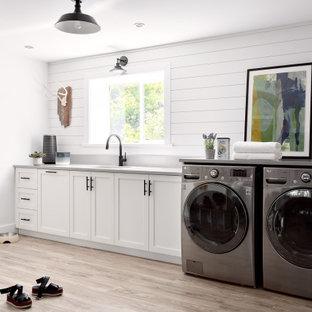 Idee per una lavanderia multiuso chic di medie dimensioni con lavello sottopiano, ante in stile shaker, ante bianche, pareti bianche, parquet chiaro, lavatrice e asciugatrice affiancate, pavimento beige, top grigio e pareti in perlinato