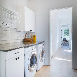 Ejemplo de cuarto de lavado lineal, escandinavo, con armarios con paneles lisos, puertas de armario blancas, encimera de acero inoxidable, paredes blancas, suelo de madera clara, lavadora y secadora juntas, suelo beige y encimeras grises