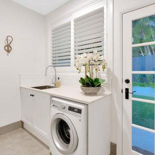 Maritim inredning av en mellanstor vita parallell vitt tvättstuga, med skåp i shakerstil, turkosa skåp, bänkskiva i kvarts, vitt stänkskydd, stänkskydd i tunnelbanekakel, vita väggar, klinkergolv i keramik och beiget golv