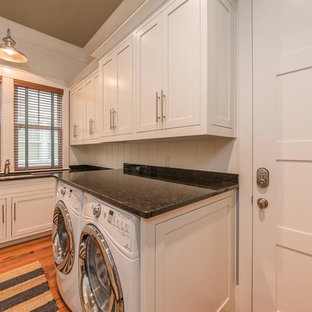 Design ideas for a medium sized rustic utility room in Atlanta with a submerged sink, shaker cabinets, white cabinets, granite worktops, white walls, medium hardwood flooring, a side by side washer and dryer, brown floors and black worktops.