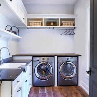 Inredning av en klassisk mellanstor svarta l-formad svart tvättstuga enbart för tvätt, med en nedsänkt diskho, skåp i shakerstil, vita skåp, bänkskiva i kvarts, grå väggar, mörkt trägolv och en tvättmaskin och torktumlare bredvid varandra