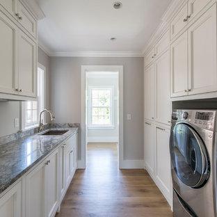 Esempio di un'ampia sala lavanderia stile marinaro con lavello sottopiano, ante bianche, top in granito, lavatrice e asciugatrice affiancate e ante a filo