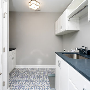 Inspiration for a mid-sized galley dedicated laundry room in Philadelphia with an undermount sink, flat-panel cabinets, white cabinets, soapstone benchtops, black splashback, grey walls, porcelain floors, a side-by-side washer and dryer, multi-coloured floor and black benchtop.