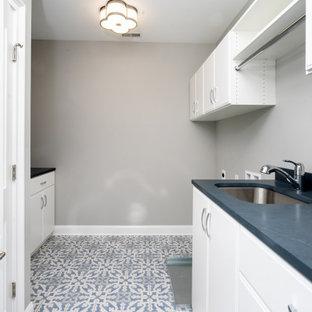 Inspiration för mellanstora parallella svart tvättstugor enbart för tvätt, med en undermonterad diskho, släta luckor, vita skåp, bänkskiva i täljsten, svart stänkskydd, grå väggar, klinkergolv i porslin, en tvättmaskin och torktumlare bredvid varandra och flerfärgat golv