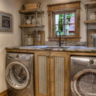 Idéer för mellanstora rustika linjära flerfärgat tvättstugor enbart för tvätt, med en undermonterad diskho, granitbänkskiva, vita väggar, mellanmörkt trägolv, en tvättmaskin och torktumlare bredvid varandra och flerfärgat golv