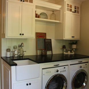 Foto på en liten lantlig tvättstuga, med en rustik diskho, luckor med infälld panel, vita skåp, bänkskiva i täljsten, gröna väggar, travertin golv, en tvättmaskin och torktumlare bredvid varandra och beiget golv