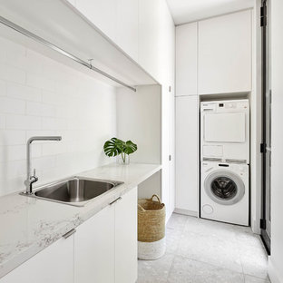 Design ideas for a modern l-shaped laundry room in Melbourne with a drop-in sink, flat-panel cabinets, white cabinets, a stacked washer and dryer, grey floor and white benchtop.