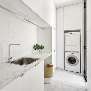 Inredning av en modern vita l-formad vitt tvättstuga, med en nedsänkt diskho, släta luckor, vita skåp, en tvättpelare och grått golv
