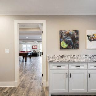Esempio di una lavanderia multiuso american style di medie dimensioni con lavello sottopiano, ante con bugna sagomata, ante bianche, top in granito, pareti grigie, pavimento in gres porcellanato, lavatrice e asciugatrice affiancate, pavimento marrone e top multicolore
