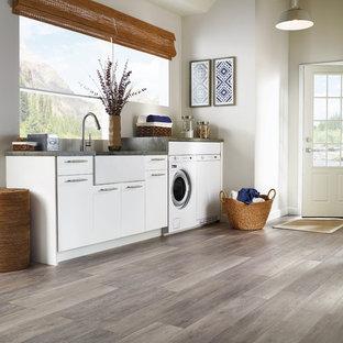 Idee per una grande lavanderia classica con lavello stile country, ante lisce, ante bianche, top in granito, pareti bianche, lavatrice e asciugatrice affiancate, pavimento in vinile, pavimento beige e top grigio