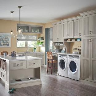 Foto di una lavanderia multiuso classica con lavello da incasso, parquet scuro, lavatrice e asciugatrice affiancate, ante con riquadro incassato, ante grigie e pareti beige