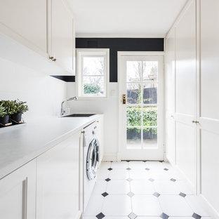 Foto di una sala lavanderia design di medie dimensioni con ante in stile shaker, ante bianche, top in quarzo composito, pareti nere, pavimento con piastrelle in ceramica, lavatrice e asciugatrice affiancate, pavimento multicolore, top bianco e lavello sottopiano