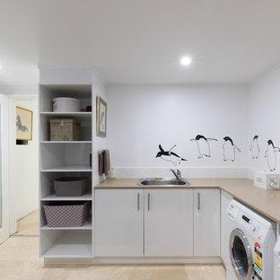 Cette photo montre une grand buanderie parallèle moderne avec un évier 2 bacs, un placard à porte plane, un plan de travail en granite, un sol en carrelage de céramique, un sol beige et des portes de placard blanches.