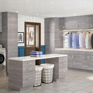 Bild på en mycket stor funkis beige l-formad beige tvättstuga enbart för tvätt, med släta luckor, bruna skåp, bänkskiva i kvarts, vita väggar, klinkergolv i porslin, en tvättmaskin och torktumlare bredvid varandra och beiget golv