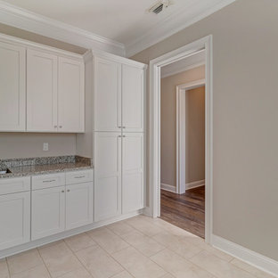 Inspiration for a large rural single-wall separated utility room in Jacksonville with a submerged sink, shaker cabinets, white cabinets, granite worktops, grey walls, ceramic flooring, a side by side washer and dryer, beige floors and multicoloured worktops.