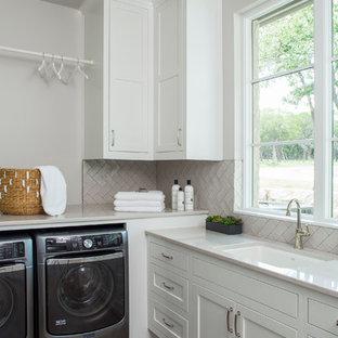 Ispirazione per una lavanderia classica con lavello sottopiano, ante in stile shaker, ante bianche, pareti bianche, pavimento in legno massello medio e lavatrice e asciugatrice affiancate