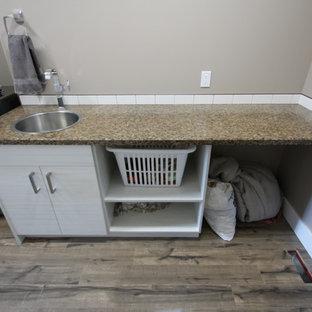 Immagine di una piccola sala lavanderia moderna con lavello a vasca singola, ante lisce, ante bianche, top in laminato, pareti beige, pavimento in legno massello medio e lavatrice e asciugatrice affiancate