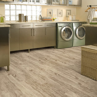 Inspiration for an expansive tropical l-shaped dedicated laundry room in Miami with flat-panel cabinets, stainless steel cabinets, vinyl floors, a side-by-side washer and dryer and beige walls.