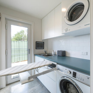 Dedicated laundry room - small contemporary galley concrete floor and gray floor dedicated laundry room idea in Canberra - Queanbeyan with a single-bowl sink, raised-panel cabinets, white cabinets, laminate countertops, white walls, a stacked washer/dryer and blue countertops