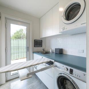 Modern inredning av en liten blå parallell blått tvättstuga enbart för tvätt, med en enkel diskho, luckor med upphöjd panel, vita skåp, laminatbänkskiva, vita väggar, betonggolv, en tvättpelare och grått golv