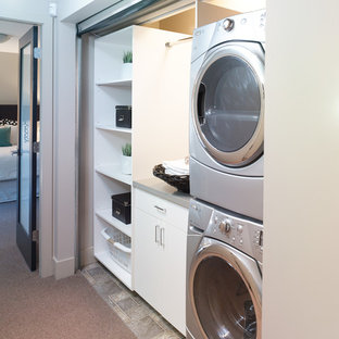 Small trendy dedicated laundry room photo in Vancouver with flat-panel cabinets, white cabinets and a stacked washer/dryer