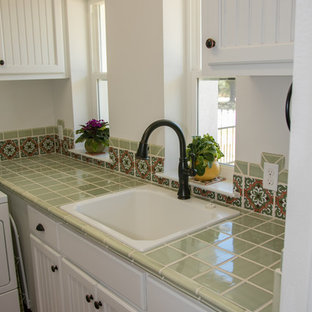 Large mediterranean l-shaped separated utility room in Austin with a built-in sink, recessed-panel cabinets, white cabinets, tile countertops, white walls, terracotta flooring, brown floors and green worktops.