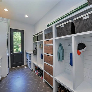 Utility room - mid-sized transitional galley porcelain tile utility room idea in Chicago with a drop-in sink, recessed-panel cabinets, white cabinets, solid surface countertops, white walls and a stacked washer/dryer