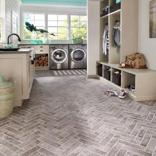 Inspiration för en maritim u-formad tvättstuga enbart för tvätt, med en tvättmaskin och torktumlare bredvid varandra och grått golv