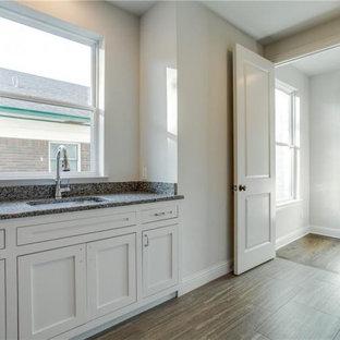 Idéer för stora vintage grått tvättstugor enbart för tvätt, med en enkel diskho, luckor med infälld panel, vita skåp, bänkskiva i kvartsit, grått stänkskydd, grå väggar, klinkergolv i porslin, en tvättmaskin och torktumlare bredvid varandra och grått golv