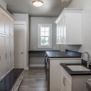 Esempio di una lavanderia multiuso american style di medie dimensioni con lavello sottopiano, top in granito, pavimento in legno massello medio, lavatrice e asciugatrice affiancate, ante in stile shaker, ante bianche, pavimento marrone e pareti grigie