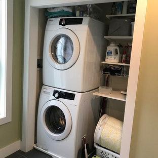 Esempio di una lavanderia chic con pareti verdi, pavimento in ardesia, lavatrice e asciugatrice a colonna e pavimento nero