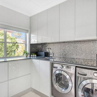 Esempio di una sala lavanderia minimal con ante bianche, top in granito, lavatrice e asciugatrice affiancate, lavello sottopiano, ante lisce e top grigio