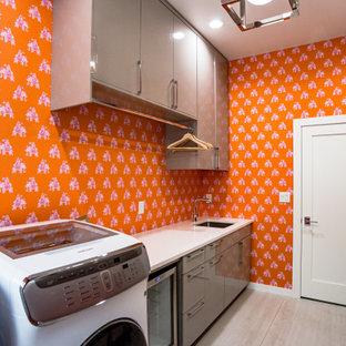 Idée de décoration pour une grande buanderie parallèle minimaliste multi-usage avec un évier posé, un placard à porte plane, des portes de placard grises, un plan de travail en granite, un mur orange, un sol en carrelage de céramique, des machines côte à côte, un sol blanc et un plan de travail blanc.