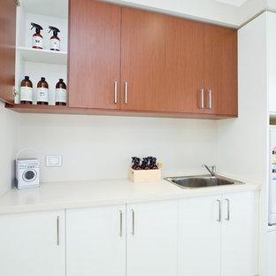 Idée de décoration pour une buanderie linéaire minimaliste dédiée et de taille moyenne avec un évier utilitaire, un placard à porte plane, des portes de placard blanches, un plan de travail en quartz modifié, un mur blanc, un sol en carrelage de porcelaine et des machines superposées.